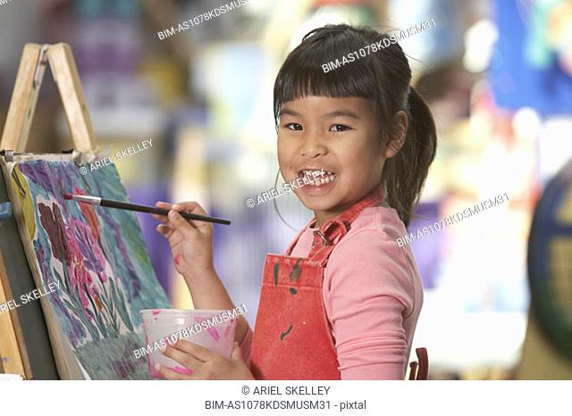 Young Asian girl painting at easel
