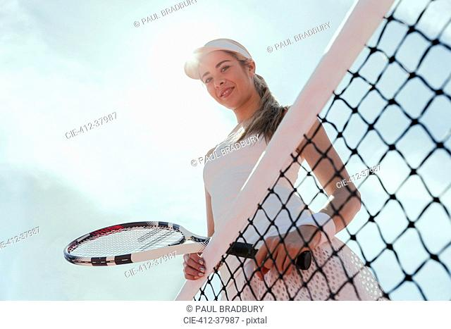 Portrait smiling, confident female tennis player holding tennis racket at net below sunny sky