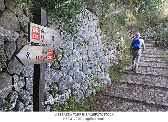 Hiking signaling and hiker on the GR221 route, between Deia and Soller, Majorca, Balearic Islands, Spain