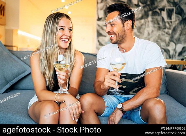 Portrait of happy couple sitting on the couch with glasses of white wine
