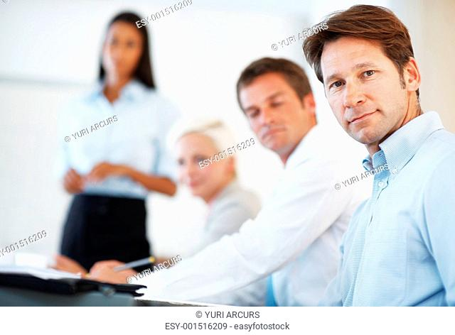 Group of businesspeople sitting together at office in a presentation giving by their colleagues
