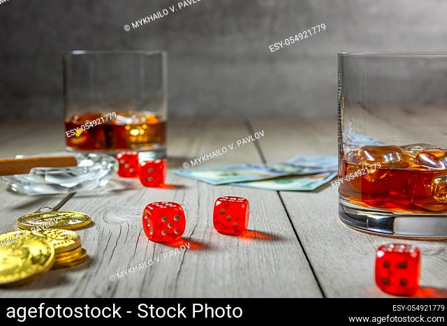Rustic wooden table. Cigar in an ashtray and Two glasses of whiskey with ice cubes. Dice and dollar bills. Few bitcoin