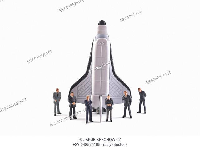 Startup concept. Figures of businessman with space shuttle on white background
