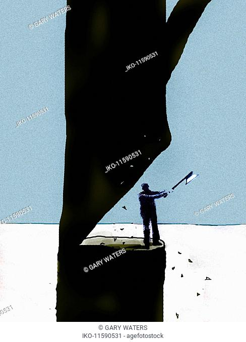Man at risk chopping down tree