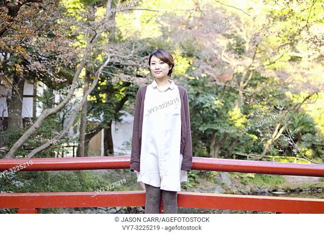 Japanese Girl poses on the street in Kamakura, Japan. Kamakura is an area located in Kanagawa where is a bit south of Tokyo