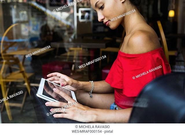 Young woman sitting in a coffee shop using tablet
