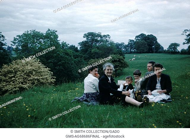 A family is sitting on the grass, two children, a man, his wife and two older women, in a large meadow with some shrubs and trees in the background, 1952