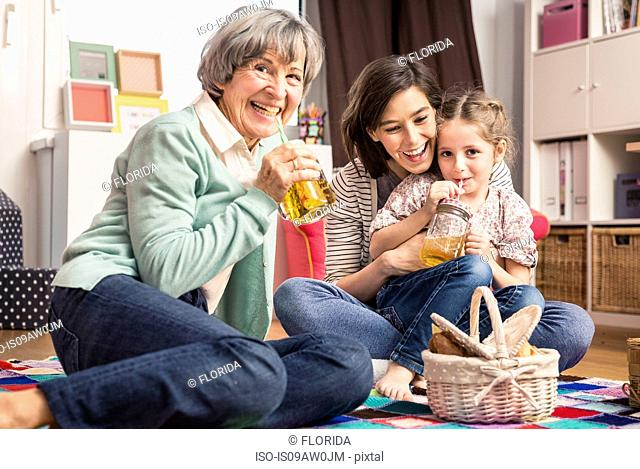 Girl with mother and grandmother having picnic on floor