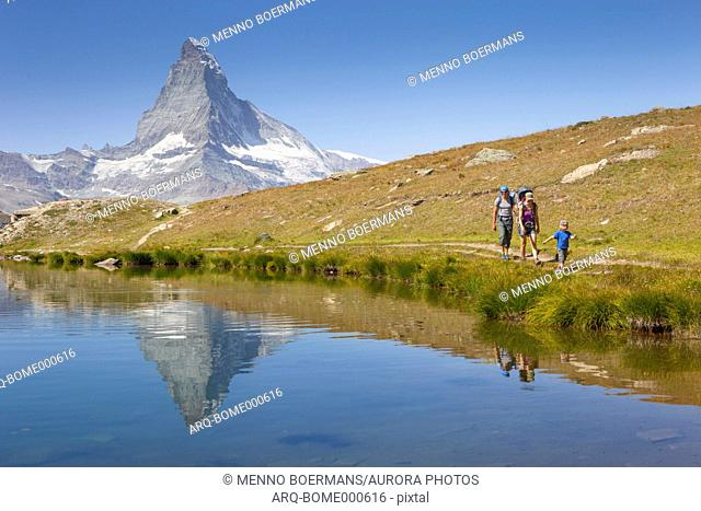 Family of mother, father and two sons hiking on lakeshore in Swiss Alps with famous Matterhorn in background, Zermatt, Valais, Switzerland