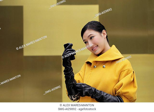 Young woman wearing black gloves looking at phone