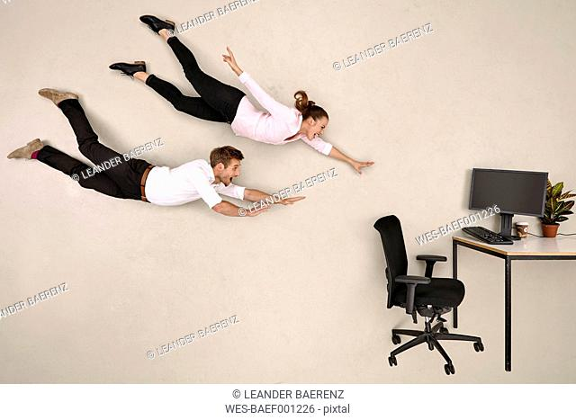 Business colleagues flying towards office desk