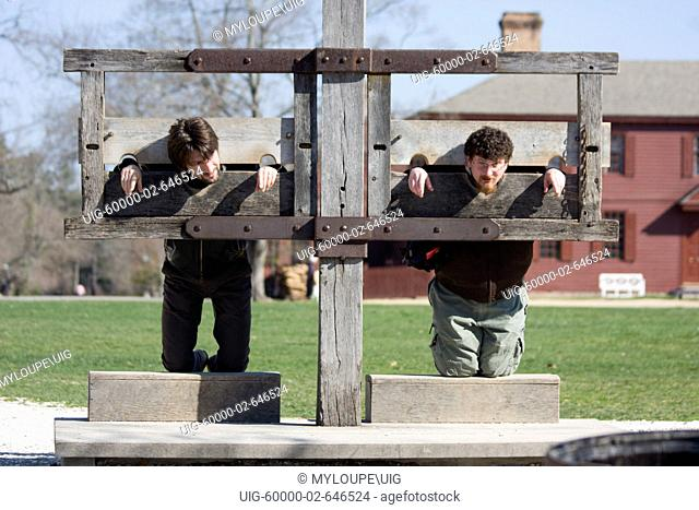 Two tourists at Colonial Williamsburg, Virginia pretend to be locked in the stockade