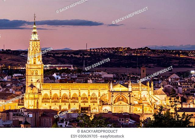 Dusk cityscape at dusk as the flood lights are illuminated on cathedral in ancient city of Toledo, Spain, Europe