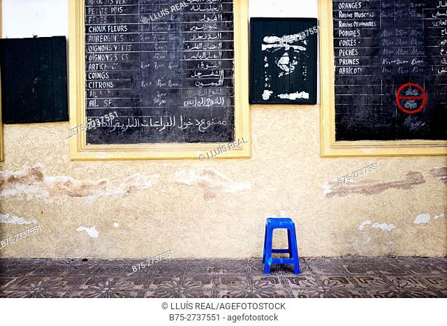 Wall at the entrance of a market with a blue stool and blackboards announcing prices of fruits and vegetables in French and Arab