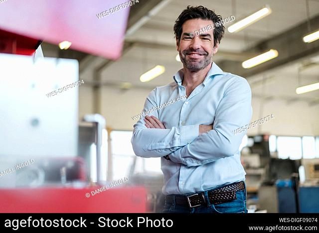 Portrait of a smiling businessman in a factory