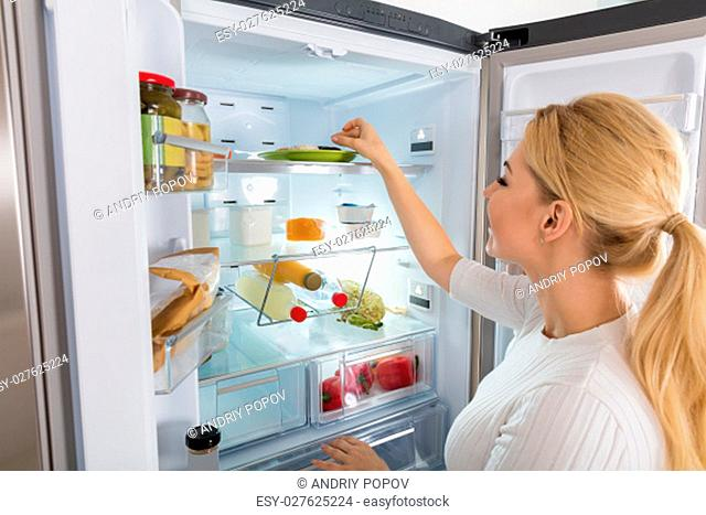 Close-up Of Young Woman Taking Food To Eat From Refrigerator