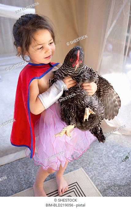 Mixed race girl holding chicken