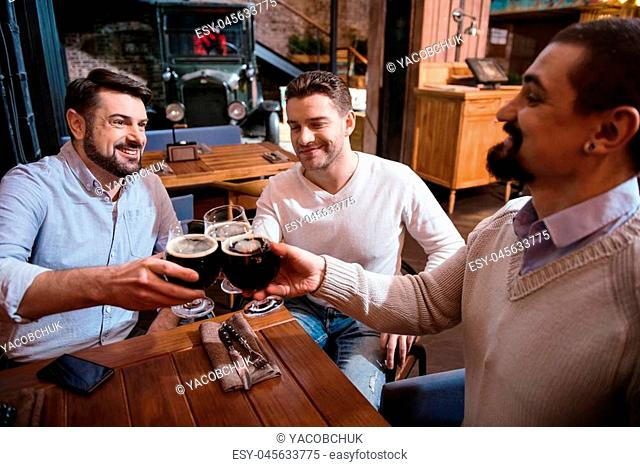 Its time to relax. Happy cheerful pleasant men cheering with glasses of beer and smiling while resting on Saturday night