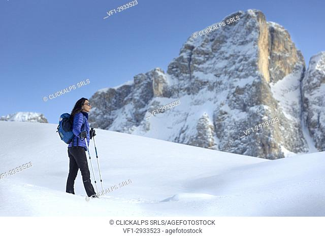 view of a model on a snow hill with Pale di San Martino in background, Trento province, Trentino Alto Adige, Italy, Europe