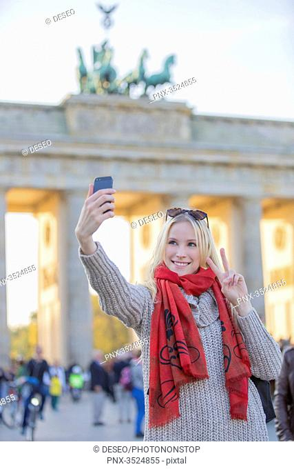 Pretty blonde woman doing a selfie in front of the Brandenburg Gate in Berlin, Germany