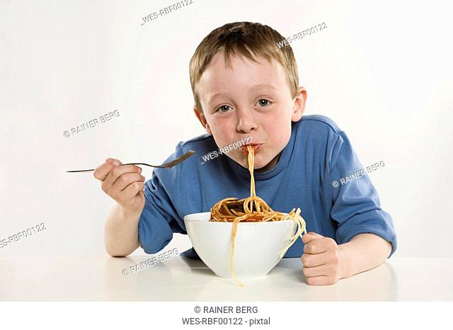 Boy 6-7 eating spaghetti, portrait