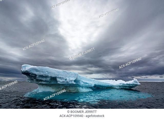 An floating iceberg slowly gives way to the Ocean's inevitable onslaught under a dramatic sky near Joinville Island, Antarctic Peninsula, Antarctica