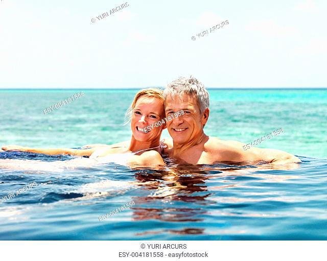 Loving mature couple enjoying their vacation in a swimming pool by the seaside
