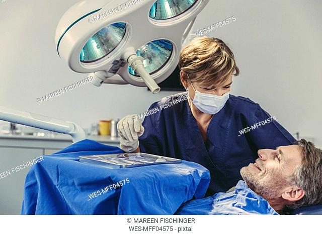 Patient smiling at dental surgeon after successful treatment