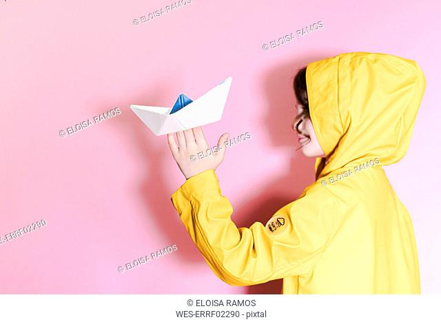 Little girl wearing an oilskin and holding a paper boat aloft