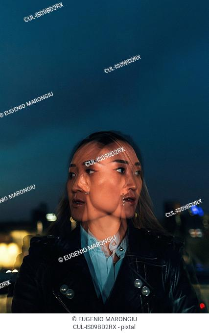 Double exposure of mid adult woman outdoors at night, pensive expression