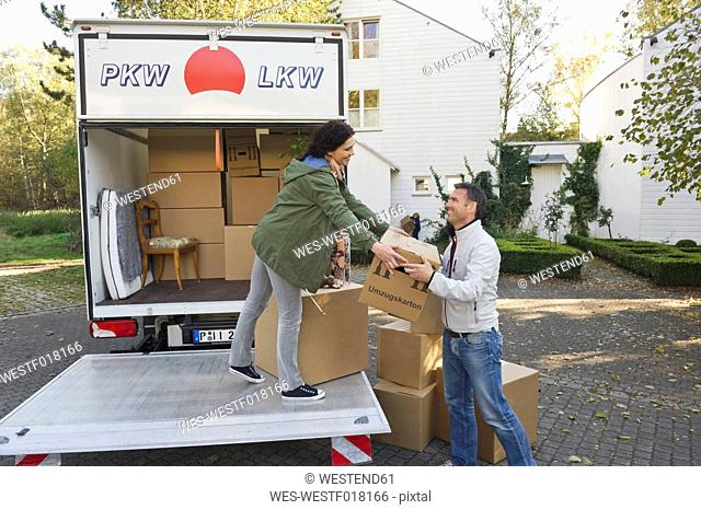 Germany, Bavaria, Grobenzell, Couple loading boxes into truck, smiling