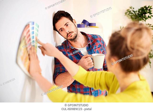 Young couple in new home, looking at paint swatches