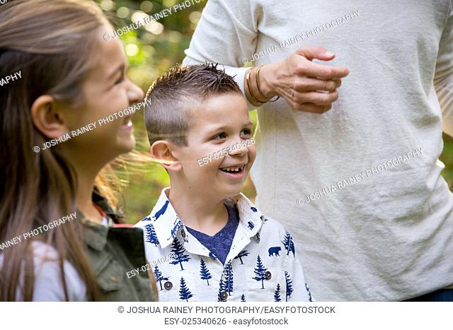 Candid lifestyle portrait of a young boy and his sister laughing and smiling at a nature park