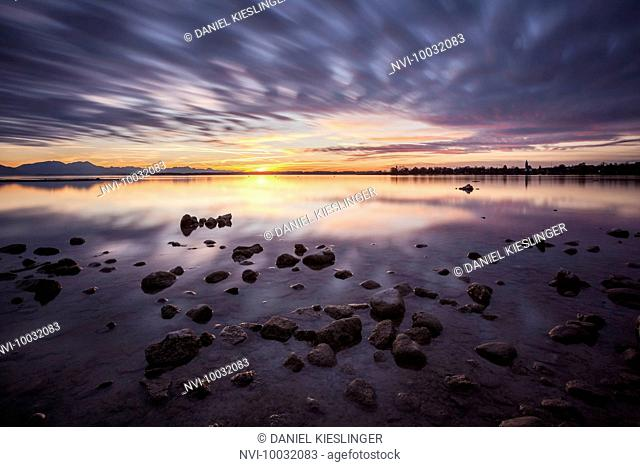 Cloudscape in the Chiemsee beach with stones and colorful clouds, Seebruck, Bavaria, Germany