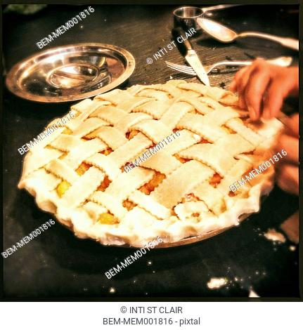 Close up of hands forming pie crust on kitchen counter