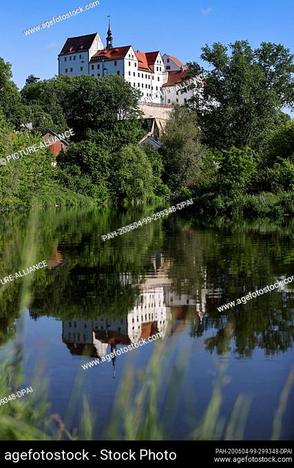 """02 June 2020, Saxony, Colditz: Colditz Castle is reflected in the Zwickauer Mulde. The """"""""Castle Colditz"""""""" is internationally famous: During the Second World War..."""