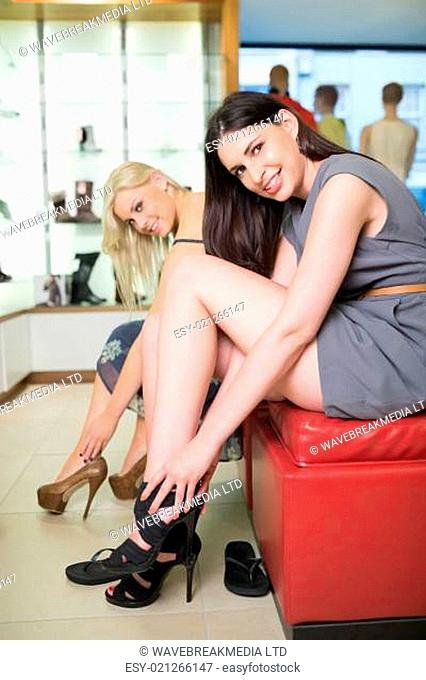 Women smiling at the camera and try on shoes