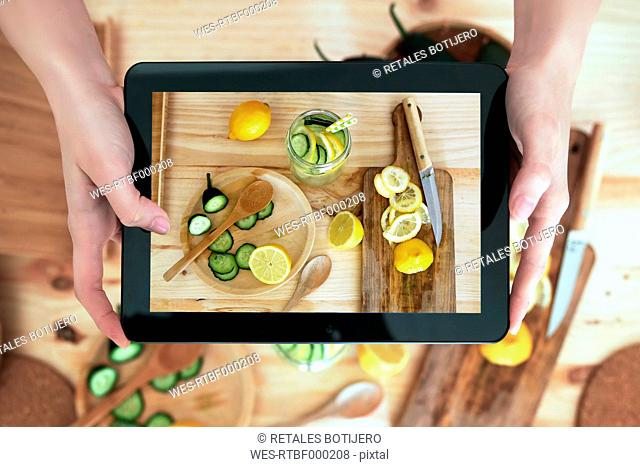Woman photographing food with digital tablet