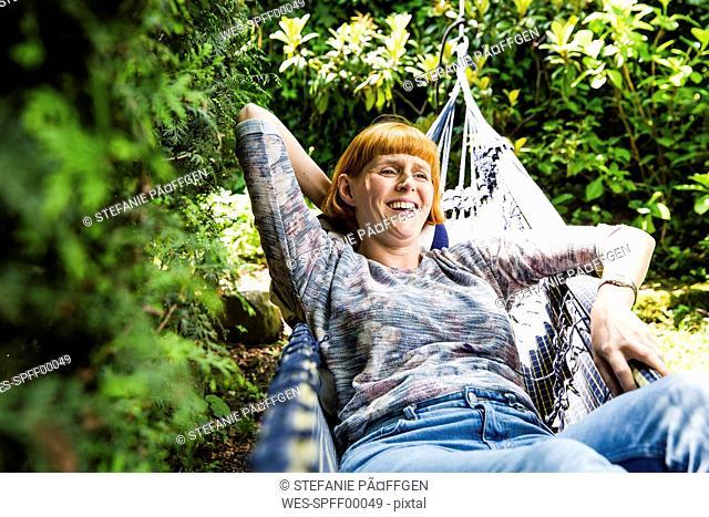 Portrait of laughing woman lying in hammock in the garden