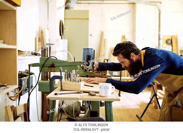 Mid adult craftsman using machine in pipe organ workshop