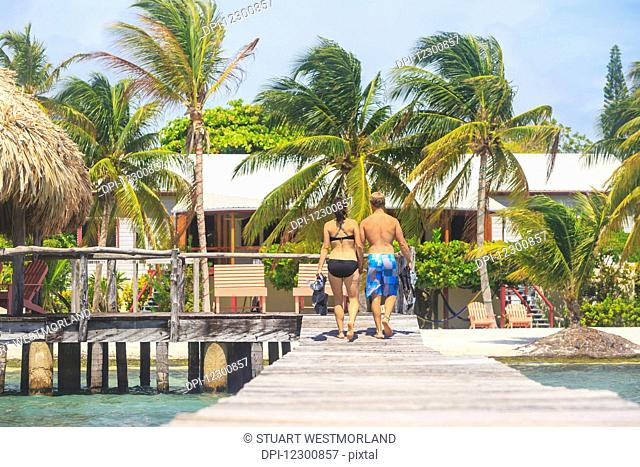 A couple walking on a wooden dock, Saint Georges Caye Resort; Belize City, Belize