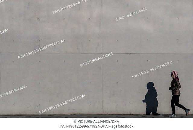 22 January 2019, Berlin: A jogger casts a shadow on a wall in the government district. Photo: Paul Zinken/dpa. - Berlin/Berlin/Germany