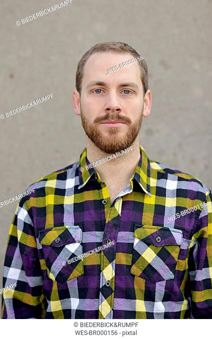Portrait of young man wearing checkered shirt