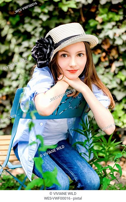 Portrait of girl wearing summer hat sitting on chair in the garden