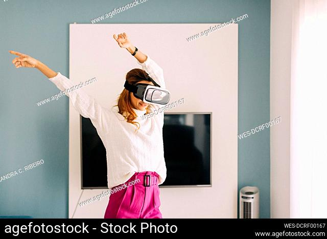 Happy young woman wearing VR glasses at home