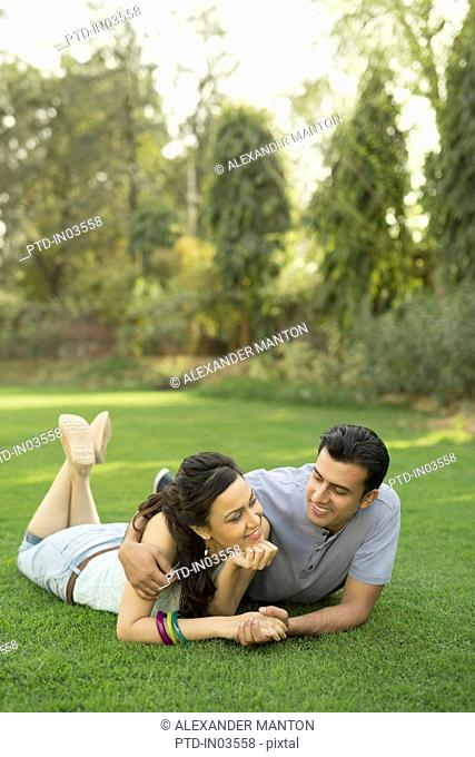 Man with arm around woman lying on grass