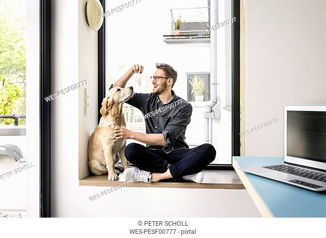 Happy man with dog sitting at the window