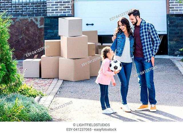 young happy family standing together in front of new house