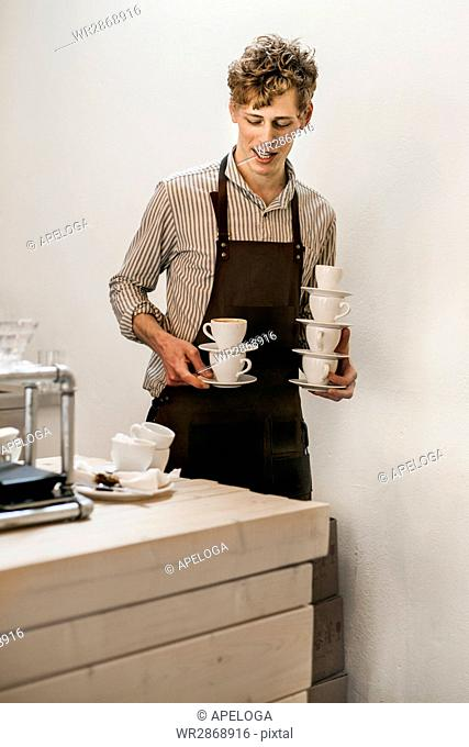 Young male barista holding empty coffee cups at cafe