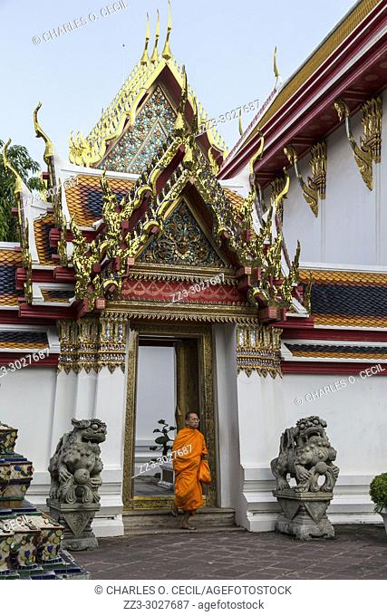 Bangkok, Thailand. Buddhist Monk in the Wat Pho (Reclining Buddha) Remple Complex. Note the Thai Architecture, showing the chofa, the curling